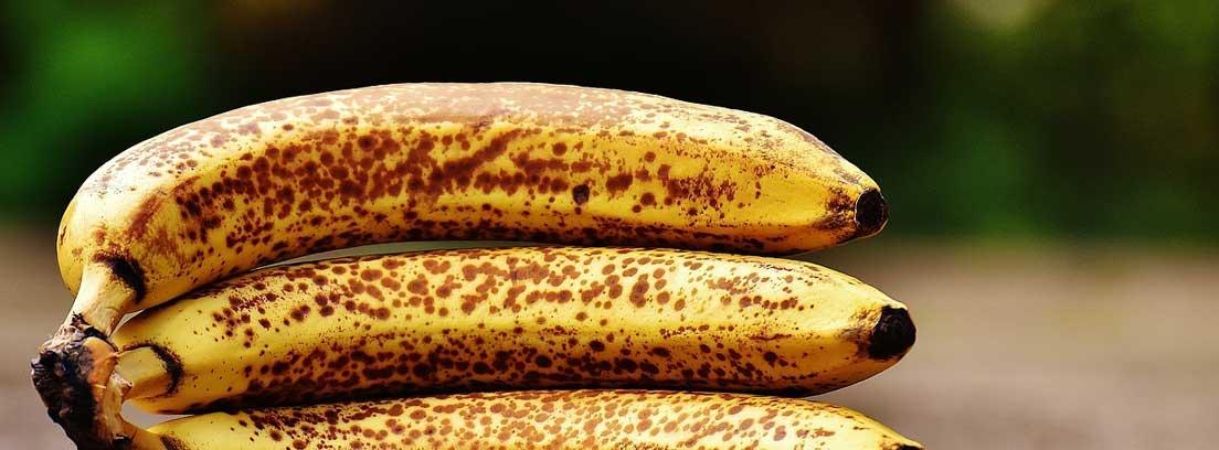 Varios plátanos maduros sobre una superficie de madera