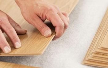 Manos colocando un suelo de tarima flotante sobre una plancha de foam