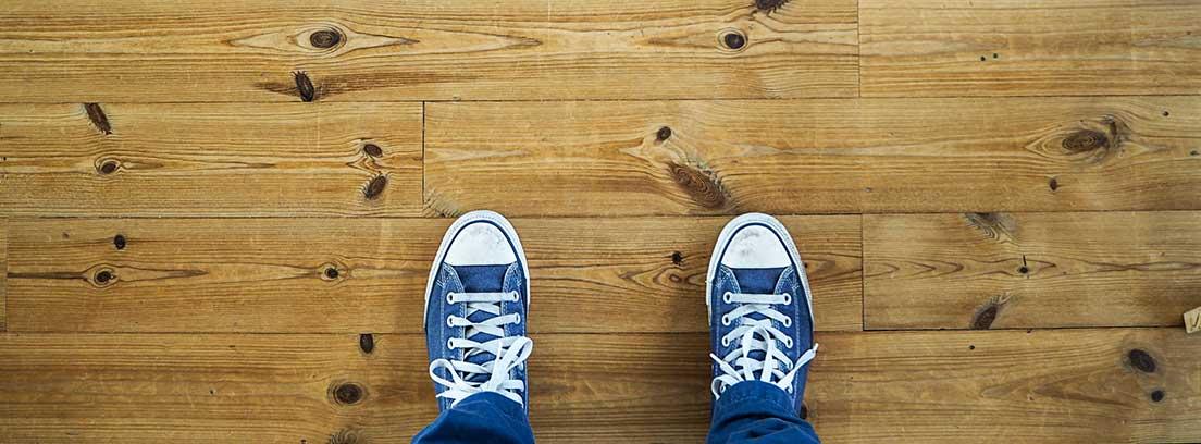 Vista cenital de unas zapatillas sobre suelo de tarima flotante