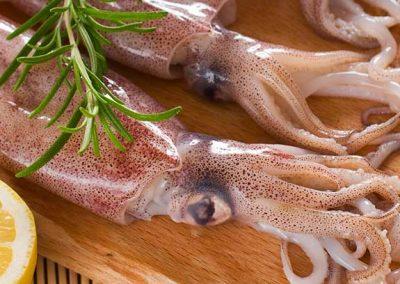 Calamares frescos en una tabla de madera junto a un cuchillo y un limón