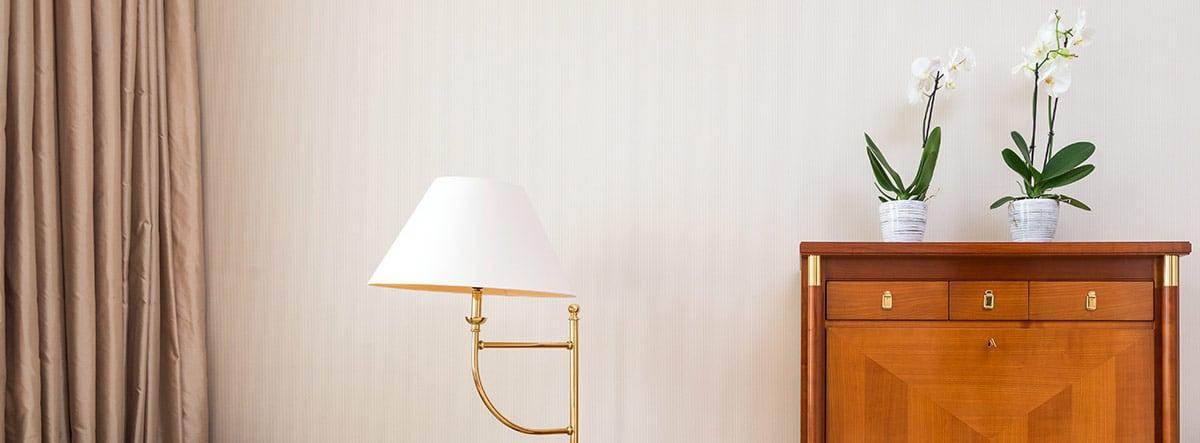 Habitación con pintura beige en las paredes, con un sofá cama y una cómoda de madera