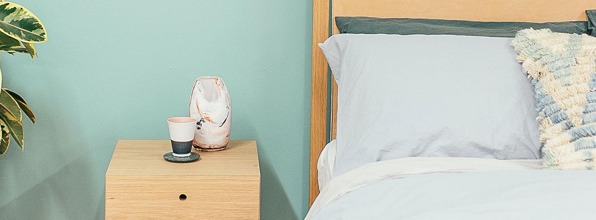 Habitación con una cama y mesita de noche, cuyas paredes son color menta.