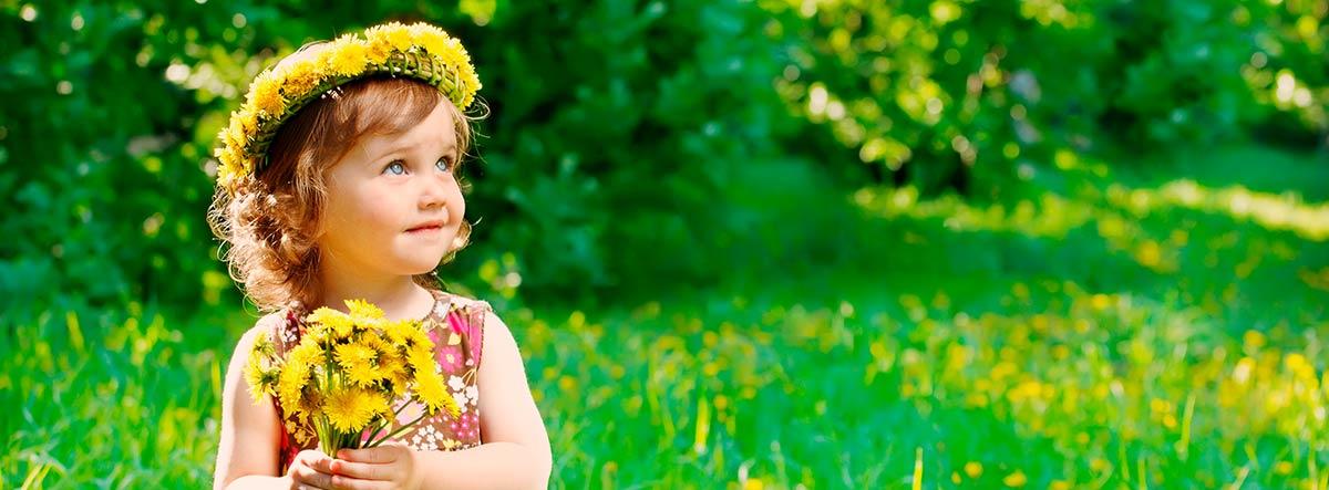 Niña con ramo y corona de flores amarillas en un jardín