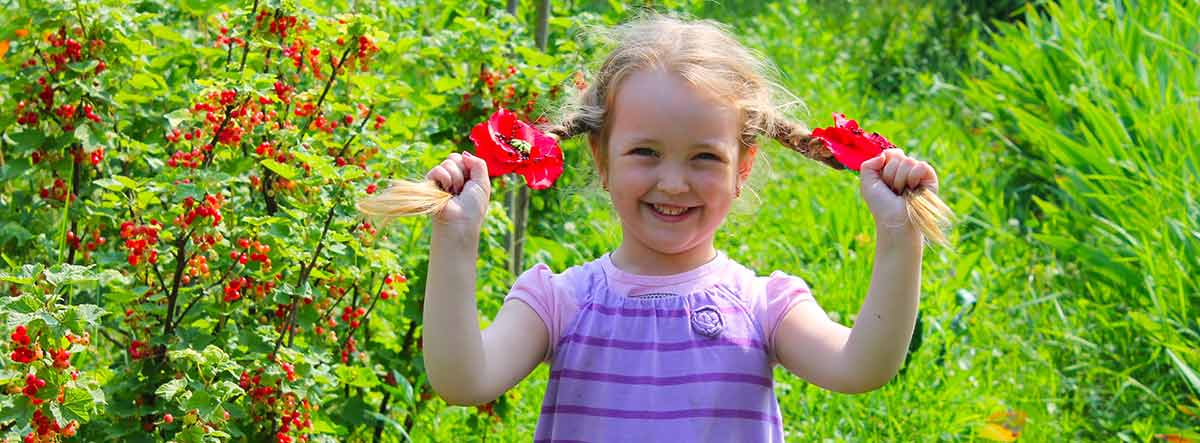 Niña sonriente en un jardín