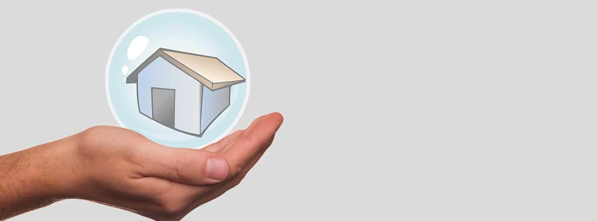 Mano sujetando una casa dentro de una burbuja