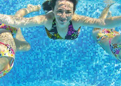 Mujer y dos niñas buceando en una piscina