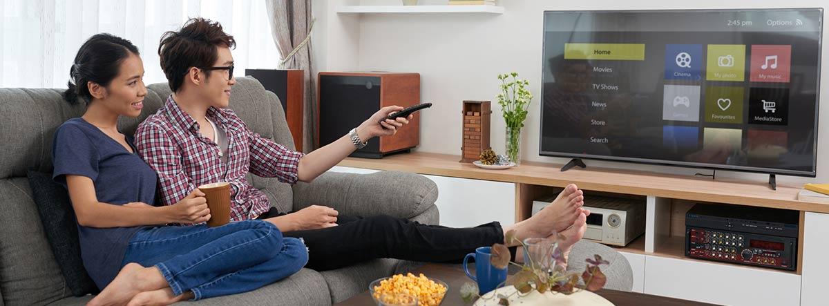 Pareja seleccionando aplicaciones en una Smart TV