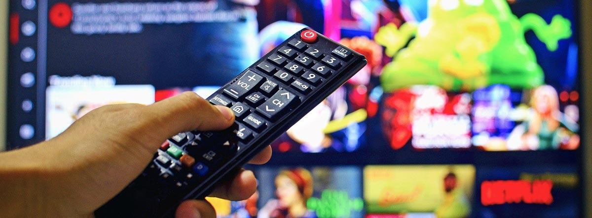 Mano apuntando con un mando a una televisión