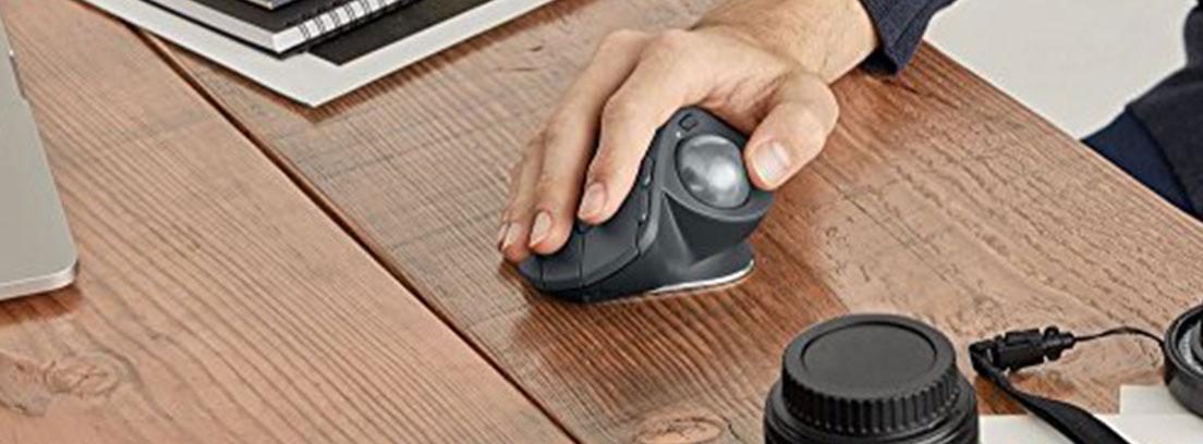 Mano sobre ratón de bola ergonómico sobre mesa de madera.