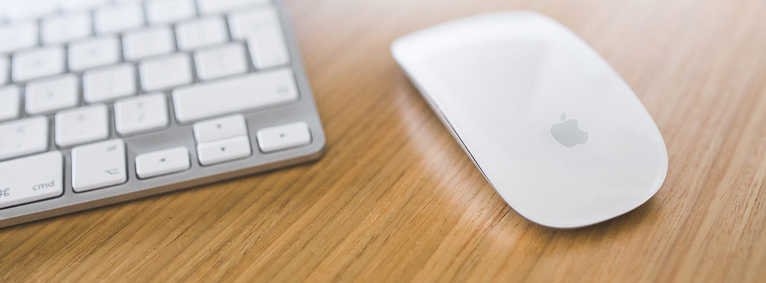 Ratón de Apple blanco sobre mesa de madera y junto a teclado.