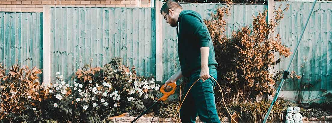 Hombre pasa cortacésped sobre hierba escasa y amarilla.