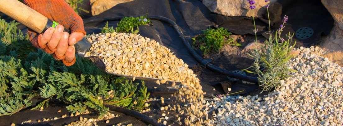 Mano sujeta pala con grava sobre el suelo de un jardín zen
