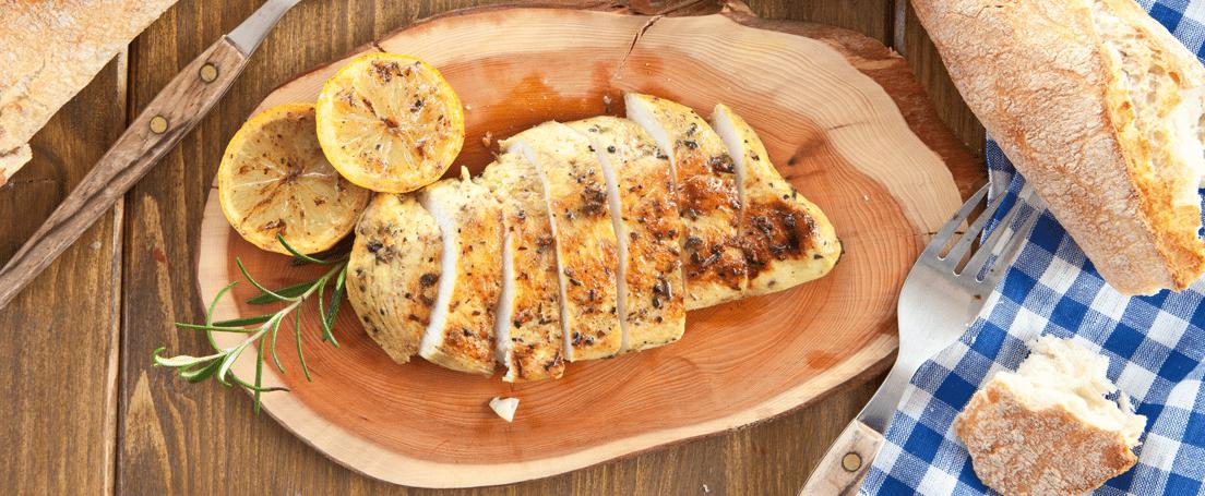 Vista cenital de una mesa con un plato con pechuga de pollo troceada y rodajas de limón, cuenco con sopa, pan y cubiertos