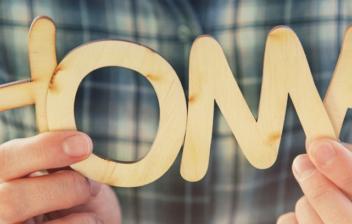 """Manos sujetando unas letras de madera formando la palabra """"home"""""""