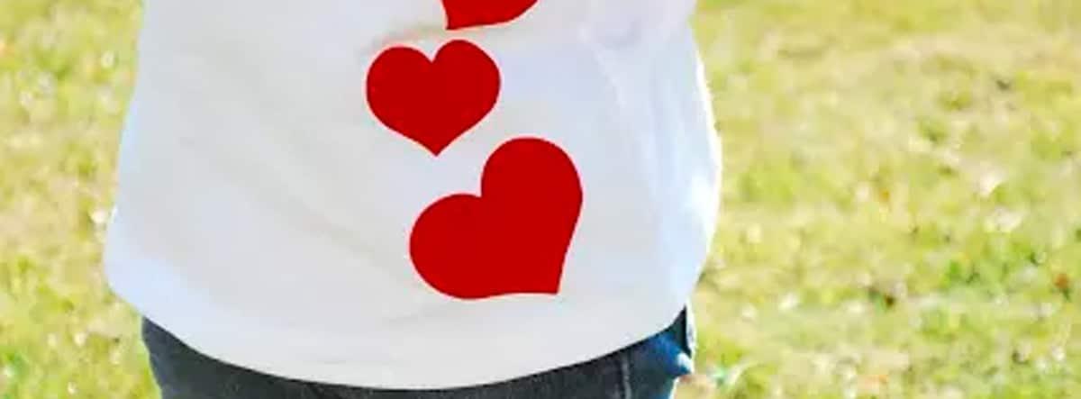 Camiseta blanca decorada con corazones rojos de fieltro