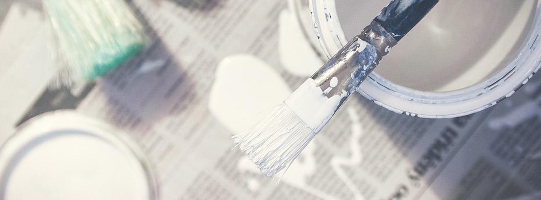 Vista cenital de un bote de pintura blanca y varias brochas de pintor.