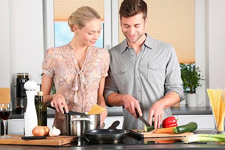 pareja en la cocina cocinando espaguetis con verdura