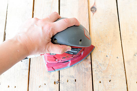 una mano cogiendo lijadora eléctrica sobre la madera