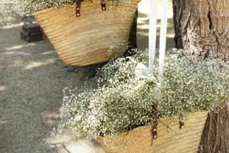 Cestas de mimbre para flores colgadas en arboles
