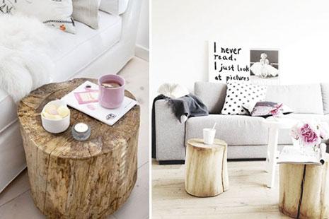 Varias mesitas de café hechas con troncos con tazas encima en un salón