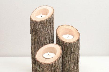 tres portavelas creados con troncos y velas encendidas