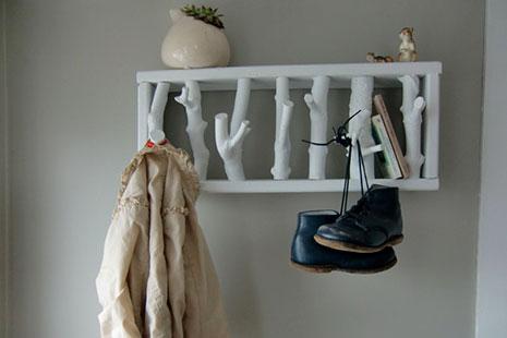 perchero hecho de troncos de color blanco con zapatos y abrigo colgados