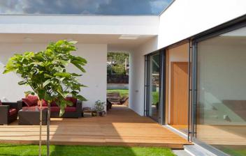 Terraza moderna con suelo de madera y césped artificial