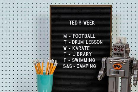 Letter board, robot de juguete y bote con lápices