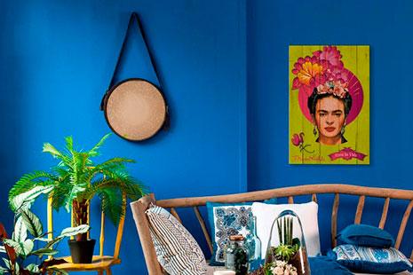 Sofá de palos de madera, alfombra amarilla con dibujos geométricos, plantas y un cuadro de Frida Kahlo pintado en madera