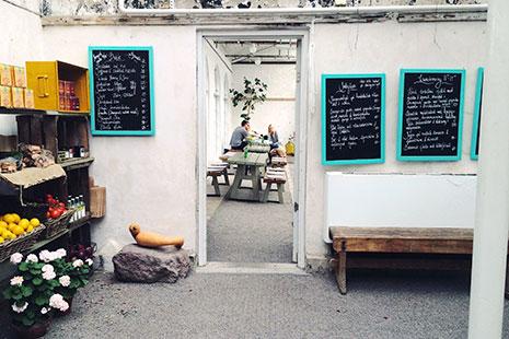 Espacio con pizarras, banco de madera y mesas al fondo decorado según la tendencia Wabi sabi