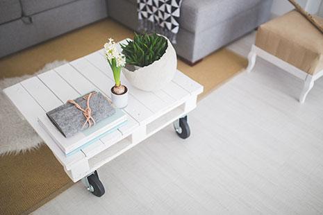 Mesa blanca de palé, sofá gris y alfombra beige