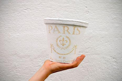 Maceta blanca con letras sobre una mano