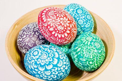 Huevos de pascua de colores con diseño de flores sobre cuenco de madera
