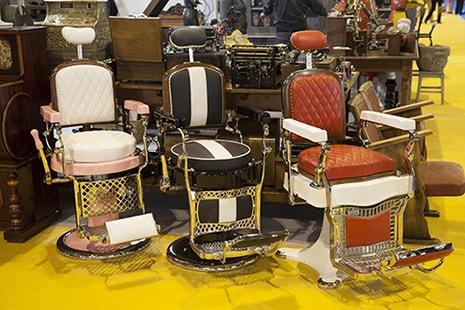 Tres sillas de barbería alineadas delante de otras piezas de mobiliario