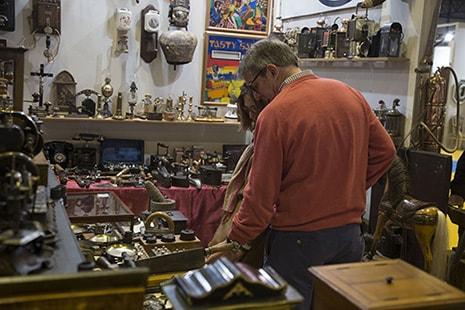 Hombre y mujer miran hacia un mostrador con muchos objetos y elementos
