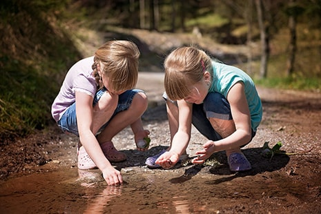Dos niñas agachadas junto al agua con piedras en sus manos