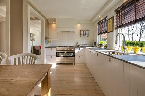 Vista general de cocina con suelo de madera y muebles blancos