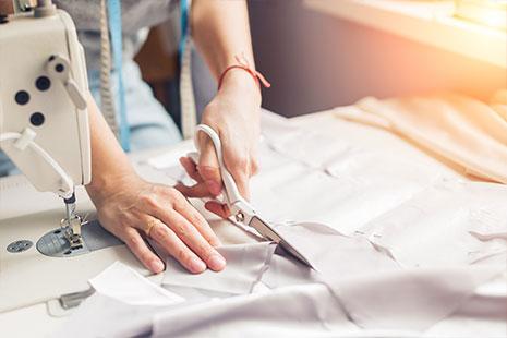 Persona cortando una tela con unas tijeras y con una máquina de coser encima de la mesa