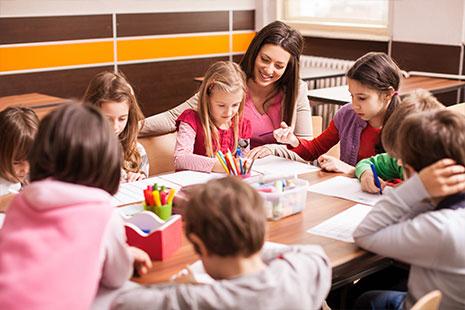 Niños comen alrededor de una mesa en el comedor de un colegio