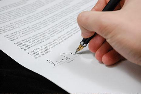 Persona firmando el acta de reunión de una comunidad de vecinos