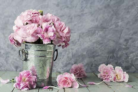 Jarrón de metal con ramo de flores lilas con pétalos esparcidos en el suelo