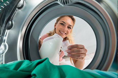 Mujer mete en una lavadora un cubo con suavizante