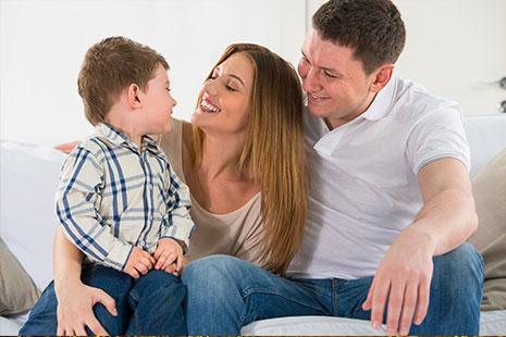 Padres jugando con su hijo en el sofá de casa