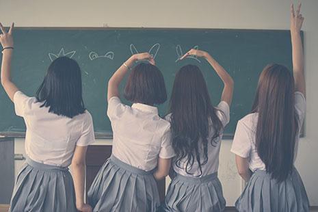 4 niñas de espaldas con camisas blancas y faldas grises sentadas sobre mesa