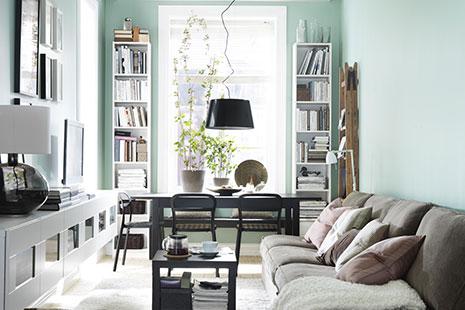 Salón de estilo nórdico con paredes verdes y muebles blancos y grises