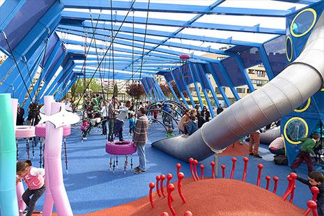 Parque infantil con estructura azul y toboganes metálicos