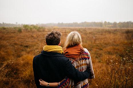 Dos personas con bufandas de espaldas y abrazadas por la cintura