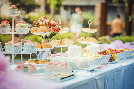 Mesa con mantel azul y diferentes fuentes con frutas, pasteles y comida diferente
