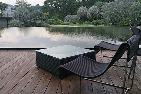 Hamacas y mesa frente a una piscina oscura