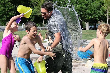 Niños mojando a su padre en verano con cubos de agua